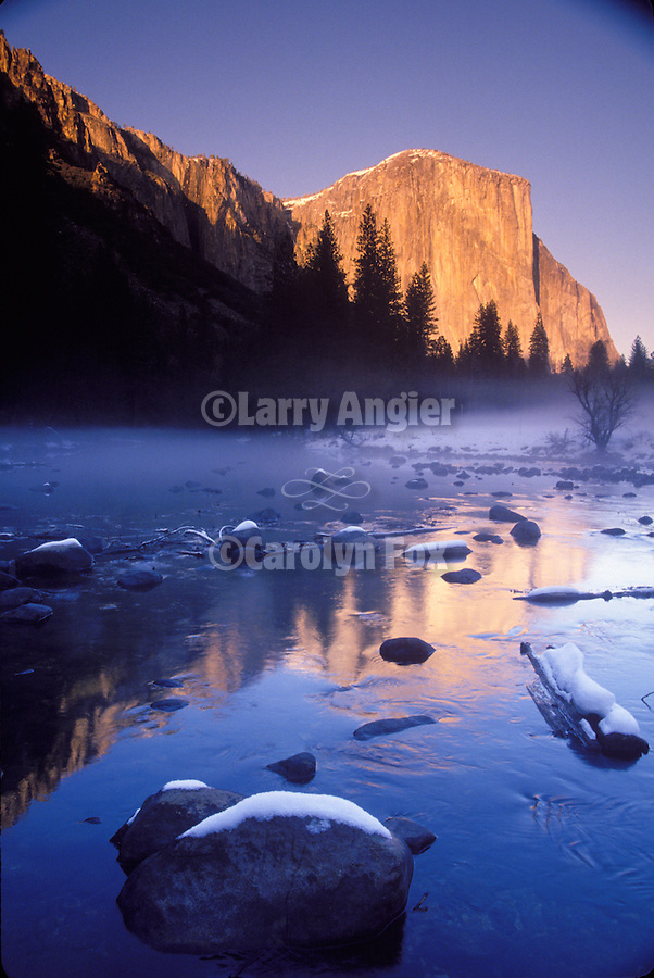 A fresh dusting of snow coats El Capitan and the Merced River at sunset in winter as the fog drifts along the river, Yosemite National Park