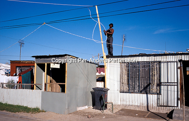 dienerg00034.Energy. A man pulling an electricity cable to his house on July 16, 2001 in Site B Khayelitsha, a township about 35 kilometers outside Cape Town, South Africa. Residents are usually stealing electricity from the minicipality as they can't afford to buy it. Khayelitsha is one of the poorest and fastest growing townships in South Africa. People usually come from the rural areas in Eastern Cape province to find work as maids and laborers. Most people don't find work and the unemployment rate is very high, together with lot of violence and a growing HIV-Aids epidemic itÕs a harsh area to live in..©Per-Anders Pettersson/iAfrika Photos.