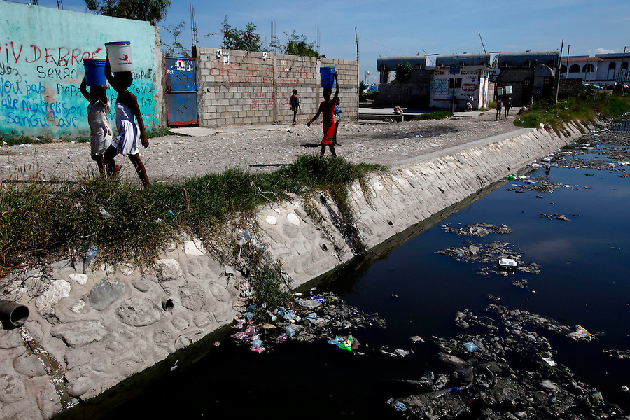 Nov 10, 2010 - Port-au-Prince, Haiti.Residents of the Cite Soleil area of Port-au-Prince, Haiti carry water gathered from a well just yards away from a river of human waste and garbage on Wednesday, November 10, 2010 as fears of a Cholera outbreak spread through the area just two days after cases of the infection were confirmed in the area, the poorest slum in Haiti's capital. Officials from the Pan American Health Organization warn that Haiti's cholera epidemic, spread primarily through consuming infected water and food, is likely to grow much larger in the wake of Hurricane Tomas.  (Credit Image: Brian Blanco/ZUMA Press)