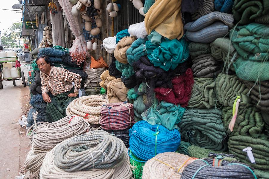 YANGON, MYANMAR - CIRCA DECEMBER 2013: Merchant in the streets of Yangon selling fishing supplies and nets.