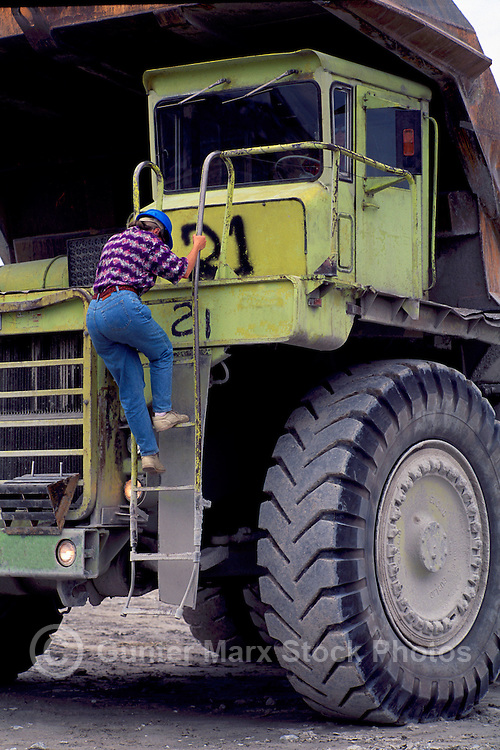 Texada Island, BC, British Columbia, Canada - Woman climbing up / down ladder on Big Mining Dump Truck at Limestone Quarry Mine (Model Released)