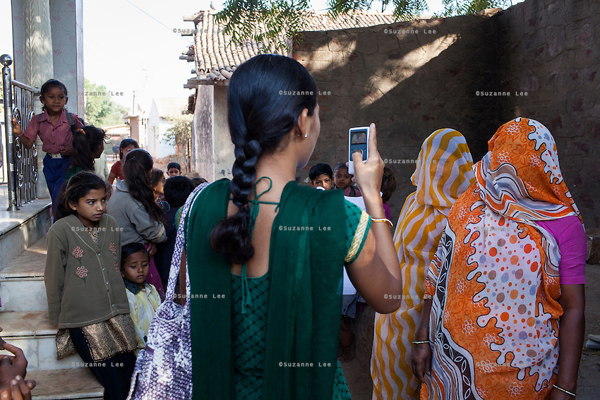 Video Volunteer videojournalist Niru J. Rathod, 24, does spot interviews with traditional women villagers on topics of caste discrimination and water quality issues in a remote village in Surendranagar, Gujarat, India on 14 December 2012. Niru, the 8th child in a family of 11 girls born to a Dalit construction worker, has been using videography for social change since 2006. She shoots and produces her own short documentaries and is a committed video activist, having conducted hundreds of village video screenings where she also speaks to thousands of men, shattering their ideas about what a woman and a Dalit can do while bringing massive changes to the communities she documents. Photo by Suzanne Lee / Marie Claire France