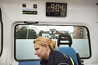 Switzerland. Canton Ticino. Pregassona.  A paramedic wears a blue uniforms and works for the Croce Verde Lugano. She sits in an ambulance during a medical emergency intervention. Digital clock. The woman is a volunteer specifically trained in emergency rescue. The Croce Verde Lugano is a private organization which ensure health safety by addressing different emergencies services and rescue services. Volunteering is generally considered an altruistic activity where an individual provides services for no financial or social gain to benefit another person, group or organization. Volunteering is also renowned for skill development and is often intended to promote goodness or to improve human quality of life. Pregassona is a quarter of Lugano.13.01.2018 © 2018 Didier Ruef