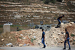 Palestinian protesters hurl stones towards Israeli troops during clashes following a demonstration near the Jewish settlement of Beit El, near Ramallah, in the occupied West Bank June 29, 2018. Photo by Shadi Hatem