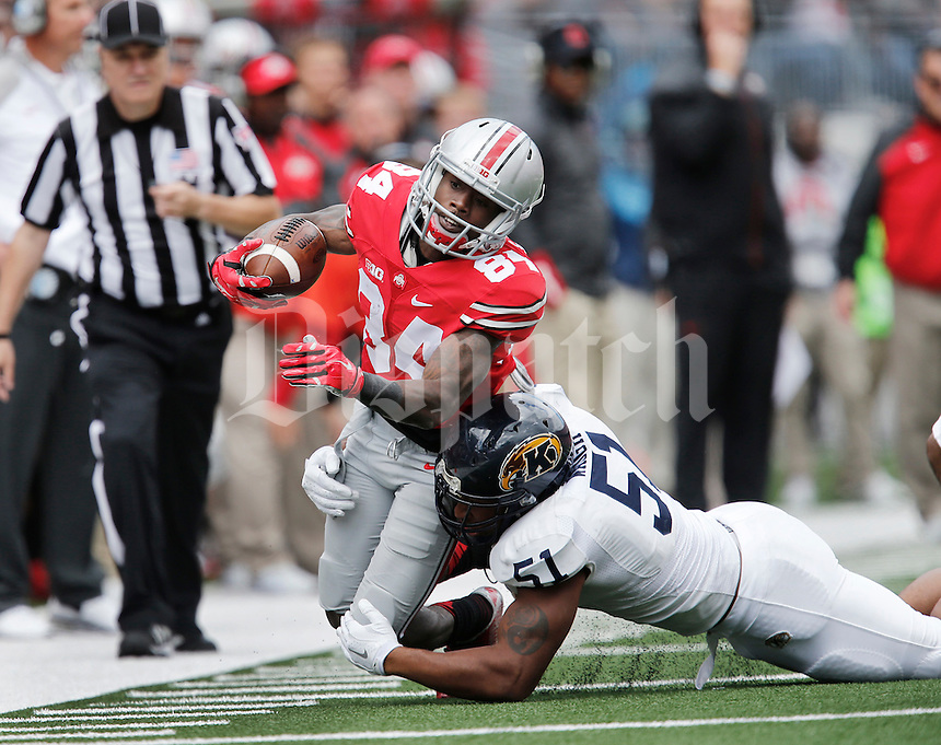 Ohio State Buckeyes wide receiver Corey Smith (84) is brought down by Kent State Golden Flashes defensive end Terence Waugh (51) in the second  quarter of a football game between The Ohio State University Buckeyes and the Kent State University Golden Flashes on Saturday, September 13, 2014 at Ohio Stadium in Columbus, Ohio. (Columbus Dispatch photo by Fred Squillante)