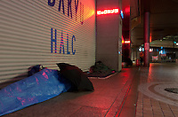 Homeless people sleep in Shinjuku's streets empty and deserted as people leave the city or stay indoors after the magnitude 9 magnitude earthquake hit the north east of Japan on March 11th. Shinjuku, Tokyo, Japan march 16th 2011