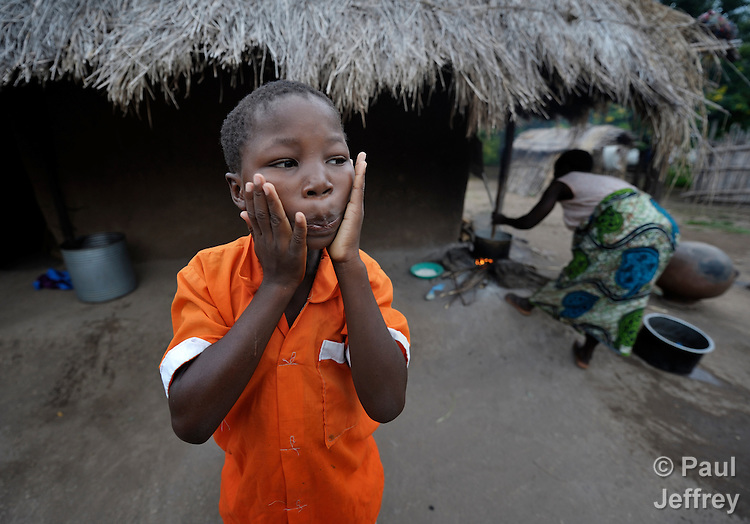 "Gota Dzongololo, 11, rubs lotion on his face in the morning after getting dressed in his school uniform. He lives in Chidyamanga, a village in southern Malawi that has been hard hit by drought in recent years, leading to chronic food insecurity, especially during the ""hunger season,"" when farmers are waiting for the harvest."