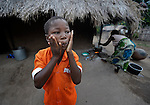 """Gota Dzongololo, 11, rubs lotion on his face in the morning after getting dressed in his school uniform. He lives in Chidyamanga, a village in southern Malawi that has been hard hit by drought in recent years, leading to chronic food insecurity, especially during the """"hunger season,"""" when farmers are waiting for the harvest."""