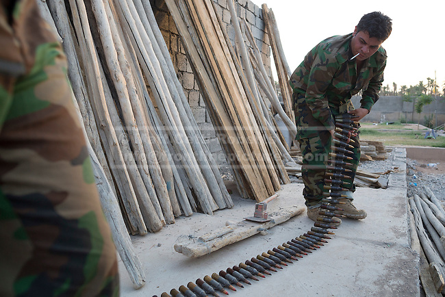 29/06/2014. Khanaqin, Iraq. Kurdish peshmerga fighters prepare ammunition for a ZPU-2 14.5mm heavy machine gun at a Kurdish peshmerga base in Khanaqin, Iraq. Counted by Kurds as part of their homeland, fighting in the nearby town of Jalawla now consists of occasional skirmishes and exchanges of fire between snipers and heavy machine guns on both sides.<br /> <br /> The peshmerga, roughly translated as those who fight, is at present engaged in fighting ISIS all along the borders of the relatively safe semi-automatous province of Iraqi-Kurdistan. Though a well organised and experienced fighting force they are currently facing ISIS insurgents armed with superior armament taken from the Iraqi Army after they retreated on several fronts. &copy; Matt Cetti-Roberts