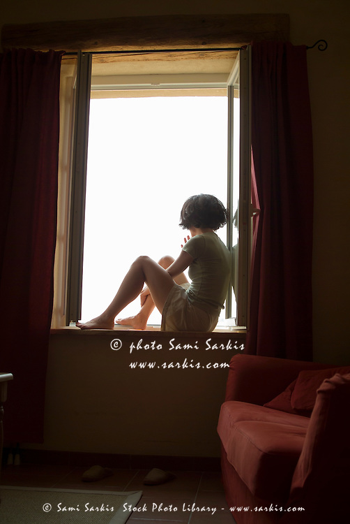 Woman sitting on her bedroom windowsill and daydreaming, France.