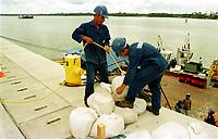 Funcionários de empresa contratada pela Texaco transportam sacos de areia para melhorar a proteção ao loado da balsa, que ontem em função da maré danificada.<br />26/02/2000.<br />Foto: Paulo Santos/Interfoto