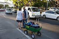 NEWLANDS, SOUTH AFRICA – FEBRUARY 7: A couple pulls a trolley after queuing for free water early in the morning from a well on February 7, 2018 at SAB breweries in Newlands, outside Cape Town, South Africa. The city of Cape Town is experiencing severe water shortage and water restrictions are in place. The big users of water are not the poor in the townships, but the wealthy people in the suburbs who have pools and gardens, and who are now forced to save on water. (Photo by Per-Anders Pettersson/)
