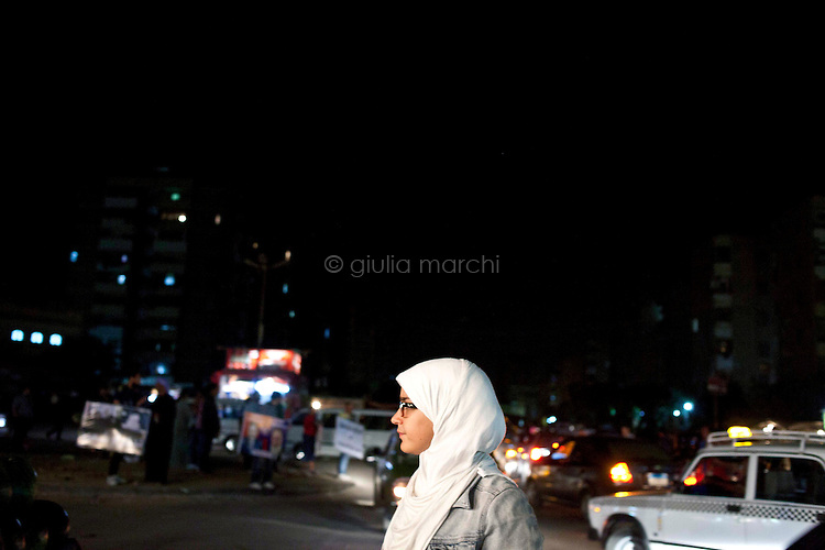 Egypt / Cairo / 10.6.2012 / Amena, one of the youngest Muslim Sister of the Nasr City's area, hands out leaflets to drivers stuck in traffic just outside of El Taba quarter, a poor area of Cairo. Egypt, June 2012.<br /> <br /> © Giulia Marchi