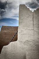 Cracking plastered adobe walls of different color and a ladder at the church at Picuris Pueblo in the Sangre de Cristo Mountains in northern New Mexico