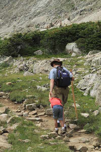 Father pulling his son along a hiking trail, Boulder, Colorado, USA.