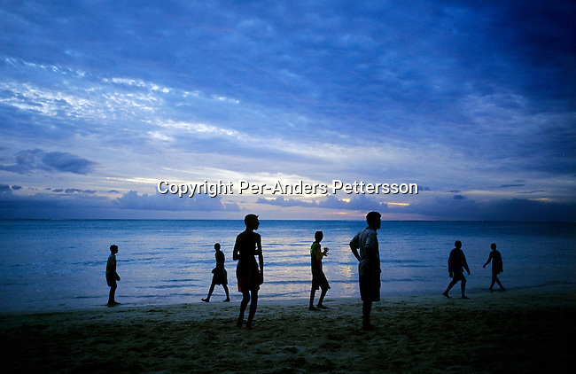 GRAND BAY, MAURITIUS - JULY 2 :  .Men play soccer on the beach as the sun sets on July 2, 2003, in Grand Bay on Mauritius. The island, located in the Indian Ocean, is a popular place for tourists with unspoiled beaches and nature. .(Per-Anders Pettersson/Getty Images).