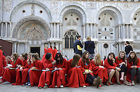 Teenager girls from a UK choral group, waiting outside St Mark's Basilica, Venice, Italy