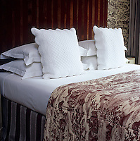 Crisp white cotton scatter cushions offset the red and white quilt and wallpaper in a London hotel bedroom