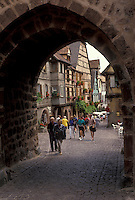 AJ2134, Alsace, France, Europe, Riquewhir, Haut Rhin, People walking on the cobbled streets in the village of Riquewhir. Through the arch half-timbered houses (Alsatian-style buildings) can be seen.