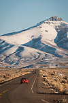 A red car drives on the highway toward the snow-covered Ruby Range in winter, Nevada