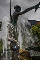 A koala perches on a rock next to an Australian Aboriginal holding a speer in one hand and boomerang in the other.  A sculpture and fountain in front of an urban office building.