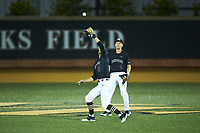Wake Forest Demon Deacons shortstop Patrick Frick (5) catches a fly ball in shallow center fielder in front of outfielder D.J. Poteet (4) during the game against the Virginia Cavaliers at David F. Couch Ballpark on May 18, 2018 in  Winston-Salem, North Carolina.  The Cavaliers defeated the Demon Deacons 15-3.  (Brian Westerholt/Four Seam Images)
