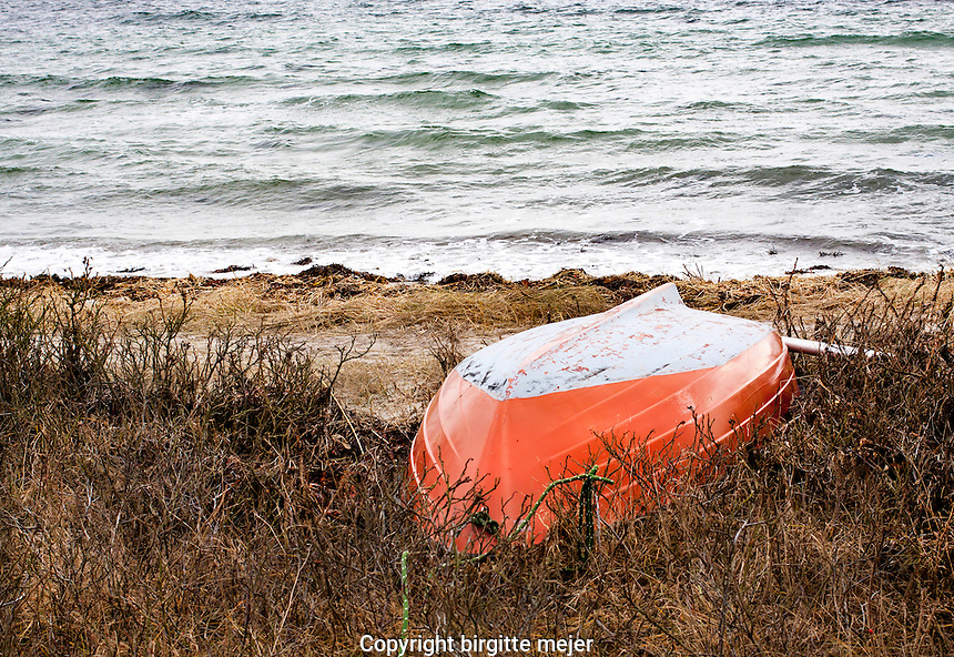 An orange and white rowing Boat lying on the Shore, waiting for summer to come