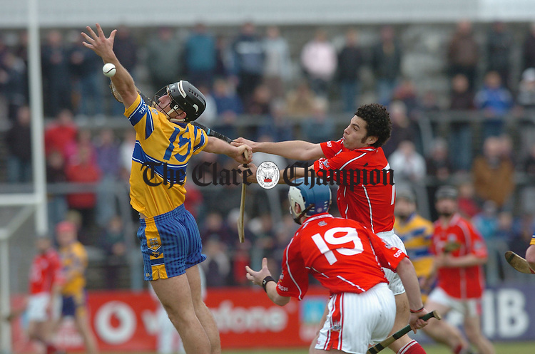 Clare's Tony Carmody in action against Cork's Sean Og O Hailpin as Cork's Kieran Murphy awaits the outcome in Cusack Park. Photograph by John Kelly.