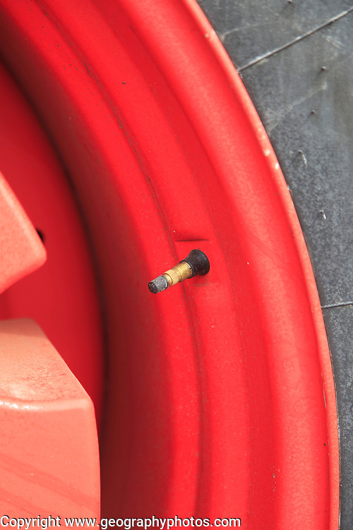 Close up of tyre air valve on red tractor wheel