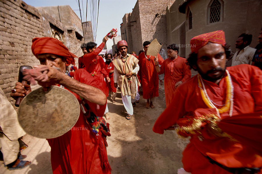 "SEHWAN SHARIF, PAKISTAN - SEPTEMBER, 2006:  Group of dervishes known as Malang, accompanying their sufi master (pir), Sheikh Akhtar Hussein Pirzada, titled as  Noor Ali Shah, during the annual celebration of Urs of Lal Shahbaz Qalandar, a 13th century Sufi Master worshiped alike by Hindus and Muslims. Born as Seyed Shah Hussain (Usman) Marandi, he later on titled as Lal (red) Shahbaz ( Falcon) Qalandar (as he belonged to Qalandria order of sufism)..Different sect of religion brings different ways of celebrating the Urs of Lal shahbaz Qalandar. Within this group of devotees, they dance as they celebrate his reunion with god and wear red clothes as he was wearing red all his life. .Wearing his traditional clothes, known as ""Dastar"", Sheikh Akhtar Hussein, visits different shrines with fellow devotees and dervishes."