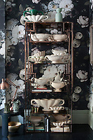 In the living room, Fulham Pottery vases are displayed on brass shelves against a dramatic backdrop of floral wallpaper designed by Ellie Cashman
