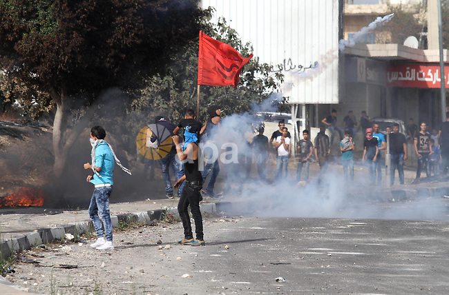 Palestinian protesters for cover from tear gas fired by Israeli security forces during clashes at the Hawara checkpoint, south of the West Bank city of Nablus, on October 13, 2015. A wave of stabbings that hit Israel, Jerusalem and the West Bank this month along with violent protests in annexed east Jerusalem and the occupied West Bank, has led to warnings that a full-scale Palestinian uprising, or third intifada, could erupt. The unrest has also spread to the Gaza Strip, with clashes along the border in recent days leaving nine Palestinians dead from Israeli fire. Photo by Nedal Eshtayah
