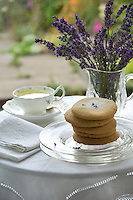 A pile of lavender shortbread biscuits and a jug of freshly cut lavender on a table