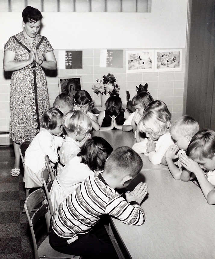 Children and teacher in prayer. 1950's.