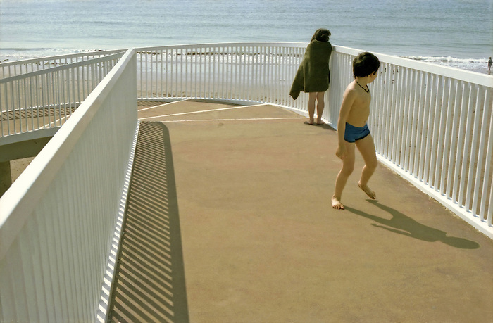 Two children, a boy and a girl, cross a footbridge after swimming in the ocean in Torquay on the South coast of England. 1980's.