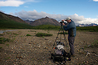 June 27, 2011, Geologist and photographer Ron Karpilo repeating a  1919 photograph by U.S. Geological Survey geologist Stephen R. Capps taken on the banks of the Teklanika River, Denali National Park and Preserve, Alaska, United States.