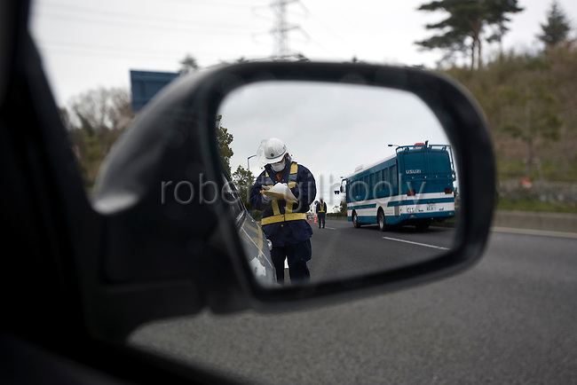 A policeman checks identification cards and other documentation at the entrance to the evacuation zone neat Tomioka Town, Fukushima Prefecture, Japan on Wednesday 20 April  2011. As of April 21, Japan has made it illegal to enter the 20 km (12 mile) zone..Photographer: Robert Gilhooly