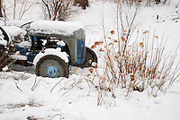 Blue and gray antique tractor in snow