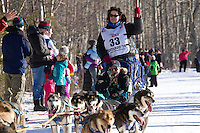 Karin Hendrickson and team run past spectators on the bike/ski trail during the Anchorage ceremonial start during the 2014 Iditarod race.<br /> Photo by Britt Coon/IditarodPhotos.com