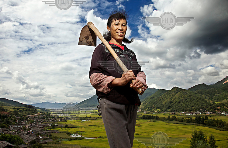 Hua (surname) Dexiang, 42, a woman from the Naxi minority, holding a mattock on a hill near her village. /Felix Features