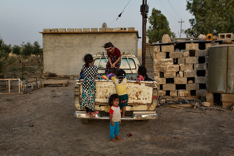 04/07/2015 -- Dibaga-Makhmur-, Iraq -- A group of displaced children play on the back of a pick up truck at the chicken farm of Dibaga. 47 families, 260 people, girls, boys, men and women now live together in one building.