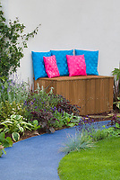 Curving Garden walkway of mixed colors leading to wooden garden bench with colorful hot pink and blue cushions, lawn grass, flowers and perennial foliage plants and ornamental grasses, daylilies Hemerocallis, hostas, Heuchera, Phormium, herb Lavendula lavender, Alchemilla, Stachys, etc