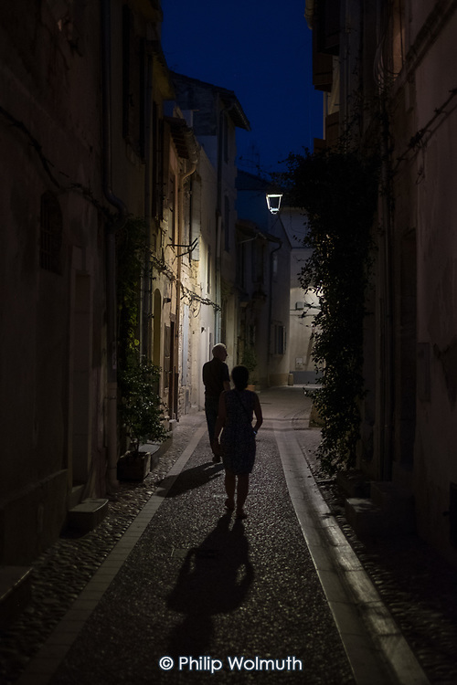 A man and a woman walk in a narrow cobbled street at night.