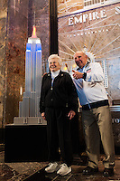 Former men's national team player Walter Bahr poses for a photo with his wife Davies next to a model of the Empire State Building lit in the Red White and Blue colors of the US Soccer Federation during the centennial celebration of U. S. Soccer in New York, NY, on April 05, 2013.