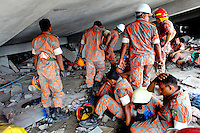 Rescue teams search for survivors on one of the floors of the collapsed Rana Plaza complex in Savar. The 8 storey building, which housed a number of garment factories employing over 3,000 workers, collapsed on 24 April 2013. By 29 April, at least 380 were known to have died while hundreds remained missing. Workers who were worried about going to work in the building when they noticed cracks in the walls were told not to worry by the building's owner, Mohammed Sohel Rana, who is a member of the ruling Awami League's youth front. He fled his home and tried to escape to neighbouring India after the building collapsed but was caught by police and brought back to Dhaka. Some of the factories working in the Rana Plaza building produce cheap clothes for various European retailers including Primark in the UK and Mango, a Spanish label. . /Felix Features