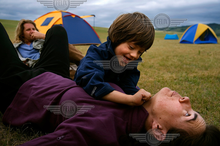 "Rowan, a five-year-old autistic child, playing with his parents during a horseback expedition across Mongolia. Rowan, who has been nicknamed ""The Horse Boy"", embarked on a therapeutic journey of discovery with his parents to visit a succession of shaman healers in one of the most remote regions in the world. Following Rowan's positive response to a neighbour's horse, Betsy, and some reaction to treatment by healers, Rowan's parents hoped that the Mongolian shamanistic rituals along the route and the prolonged contact with horses would help to unlock their son's autism and assist his development.."