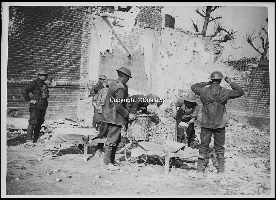 BNPS.co.uk (01202 558833)<br /> Pic: Onslows/BNPS<br /> <br /> Collecting rubble to bolster trenches. <br /> <br /> Poignant photographs revealing life on the Western Front during the First World War have emerged for sale 100 years after they were taken.<br /> <br /> The rare collection of snaps, taken in the early stages of the war, provide a moving insight into the lives of the soldiers serving on the front line.<br /> <br /> Among the archive of 70 original photographs are images of troops braving the freezing winter months in their fortified trenches at stations in France and Belgium.<br /> <br /> Particularly touching photographs show the barren 'no-man's land' between the British and German trenches.<br /> <br /> One fascinating shot shows a 'shell dump' - where 2ft tall artillery shells were stored in their hundreds while another shows soldiers manning rudimentary machine gun posts.<br /> <br /> In another, a soldier is seen loading a rocket onto a wooden launching pole which would then be fired to announce to impending attacks.<br /> <br /> The photographs are tipped to fetch 3,000 pounds when they go under the hammer at Onslows auction house in Blandford, Dorset, on July 9 on behalf of a private collector.