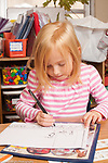 Education Elementary Kindergarten closeup of female student writing words describing her drawing or story