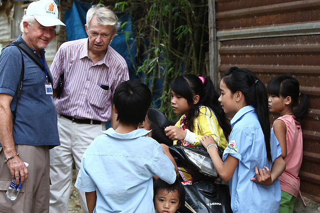Manus Campbell and Chuck Searcy of Veterans for Peace talk to children in a neighborhood in Hue, Vietnam. The group toured Vietnam in April to learn about efforts to mitigate the suffering of victims of Agent Orange and unexploded ordnance, two problems that still persist nearly four decades after the Vietnam war ended. April 22, 2013.