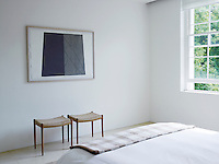 A pair of stools has been placed beneath a contemporary artwork in the bedroom